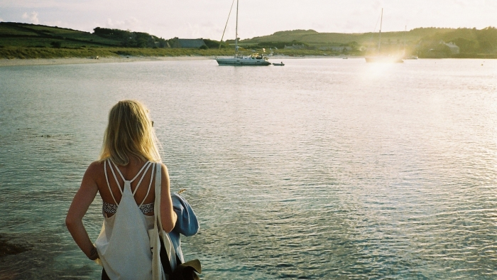 A woman looks out at the sunset on the sea at Tresco Island.
