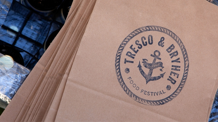 Brown paper bags with a Tresco & Bryher food festival logo on.