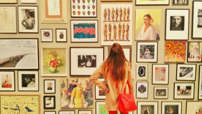 A woman stands looking at a wall covered with framed pieces of art.