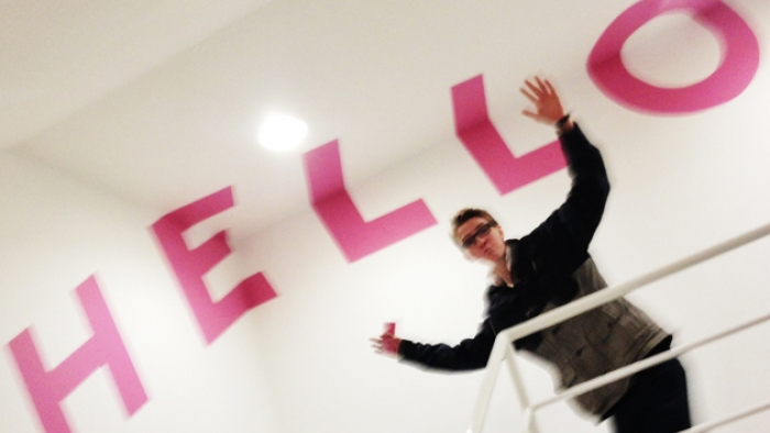 A man stands at the top of a set of stairs inside a building, with 'Hello' written on the walls and ceiling of the building.