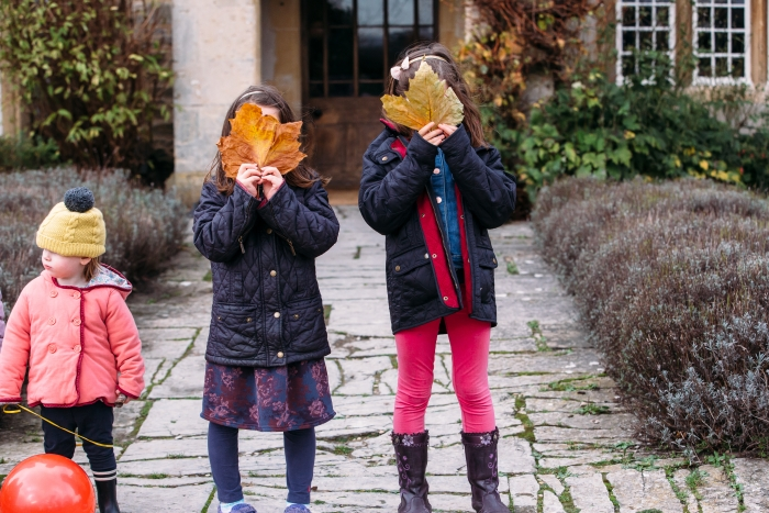 Three children standing outside an LFH hotel, two holding leaves over their faces.