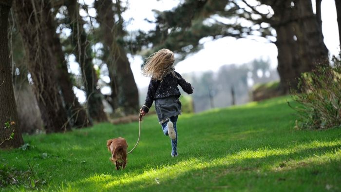 A girl and her dog running through the garden at a Luxury Family Hotel.