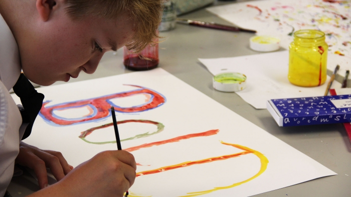 A student paints the word 'Bold' on a piece of paper in an art workshop.