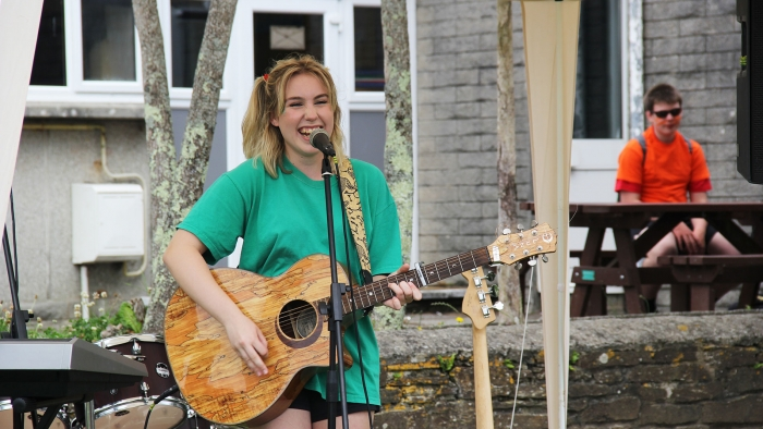 A Mounts Bay student sings and plays guitar at the school sports day.