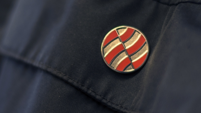 The Richfords logo as a badge on an employee's uniform.