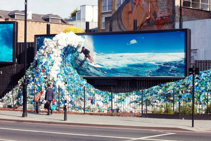 A life-sized wave made of plastic waste in front of a billboard showing surfer: part of Corona's campaign by Wieden & Kennedy Amsterdam.