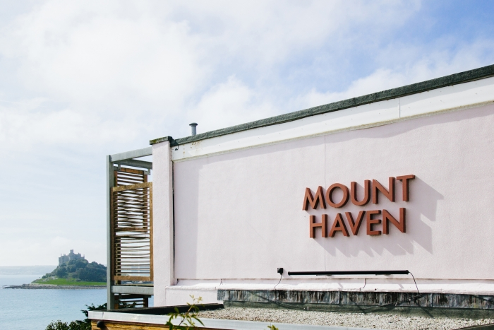 Signage reading 'Mount Haven' on the side of the hotel, with St Michael's Mount in the distance.