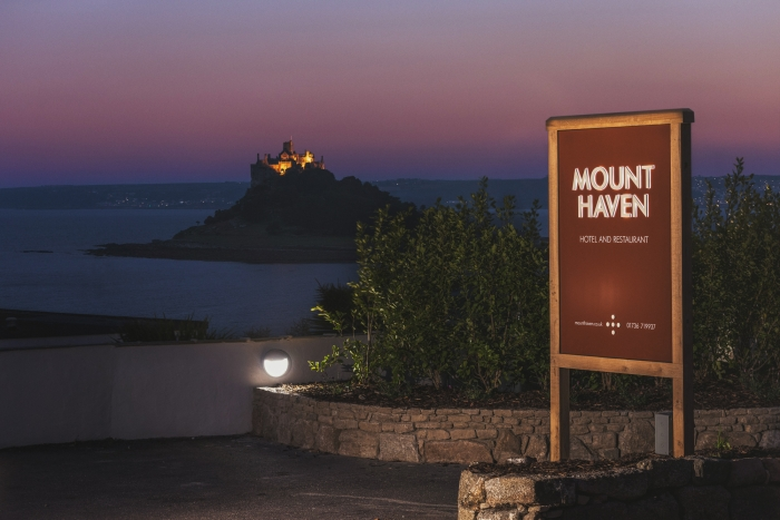 The entrance sign for Mount Haven hotel, lit up at night, with St Michael's Mount in the distance.