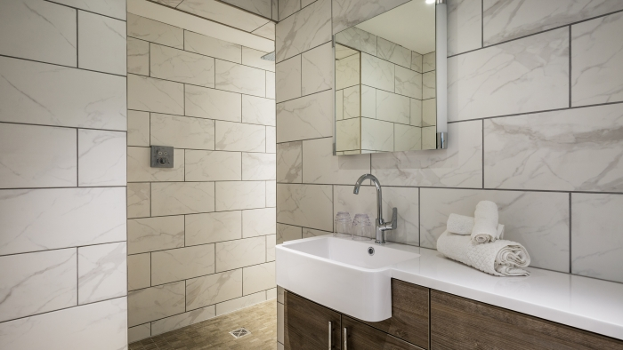 A hotel bathroom with marble tiles and a wood-cabinet sink.