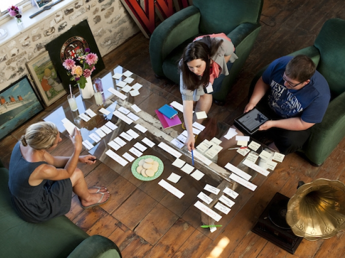 Three people sit at a glass coffee table sorting cards for a web design project.