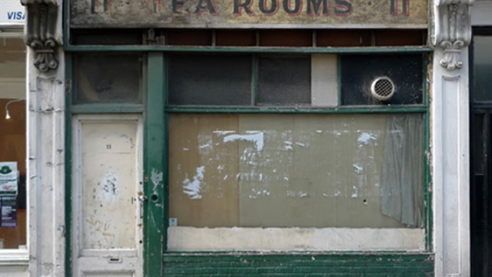 An old boarded-up shop with 'Tea Rooms' painted above it.