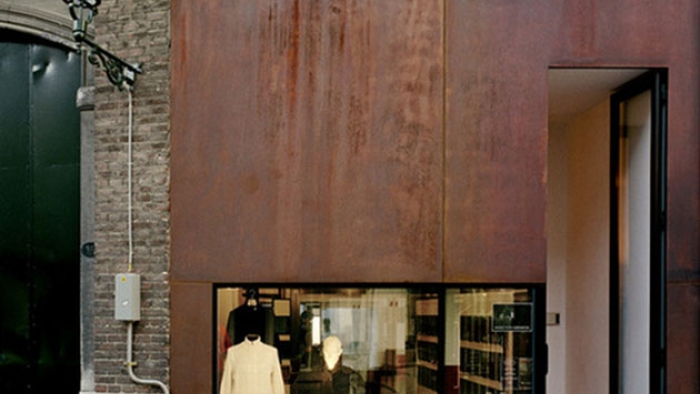 A fashion clothing shop with rusted-iron cladding in a brick building.