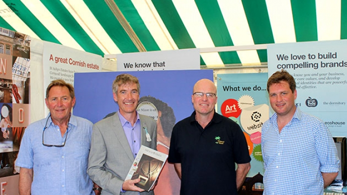 A group of men stand in a tent at Royal Cornwall Show.