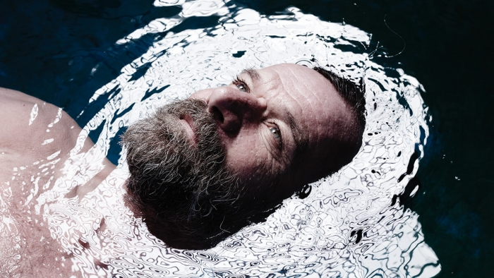 Wim Hof, a breathing expert, with his head in the water and facing upwards.