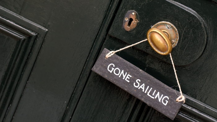 A sign reading 'gone sailing' hanging off a doorknob.