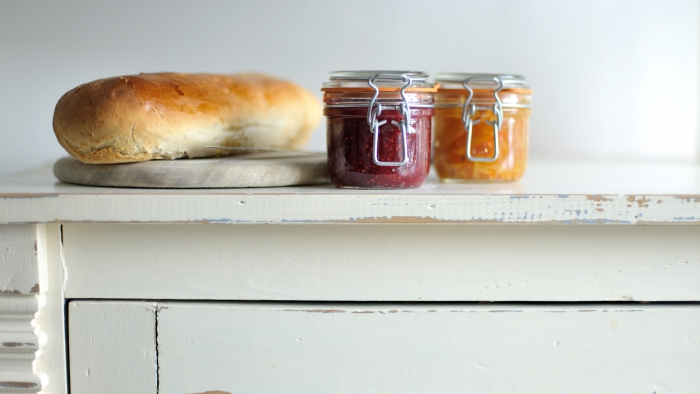 A loaf of bread and two jars of chutney on a chest of drawers.