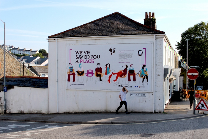 An illustrated billboard advert for Falmouth University, with the strapline 'We've saved you a place'.