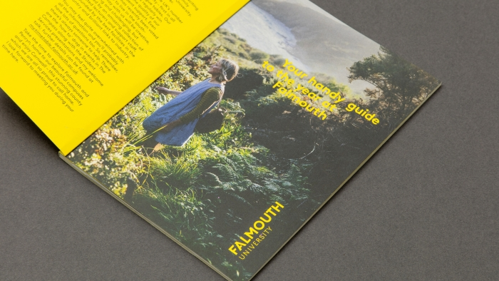 The inside cover of the Falmouth University freshers' guide, with a photo of a woman on a coastal walk.