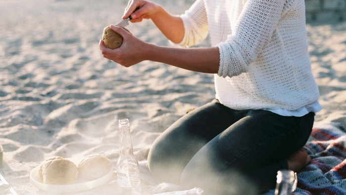 A woman cutting open potatoes on at a beach barbecue.