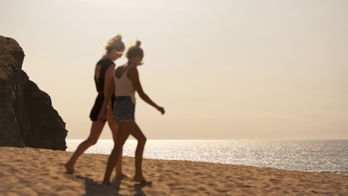 Two women walking along a Cornish beach on a sunny evening.