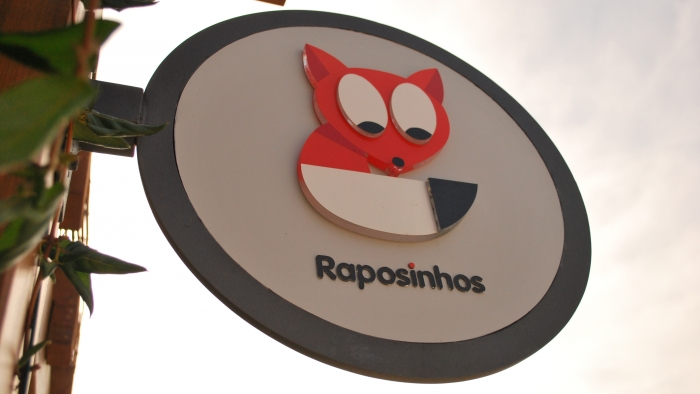 A sign with a fox logo and 'Raposinhos' on it.