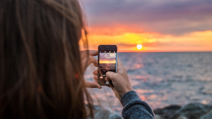 A woman takes a photo of the sunset on her iPhone.