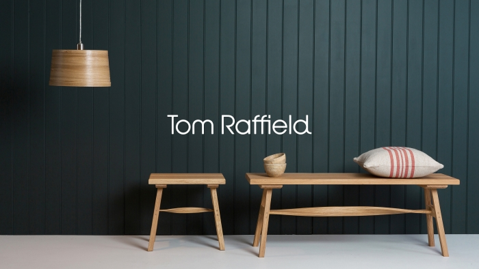 A wooden stall, bench and hanging light with the Tom Raffield Logo.