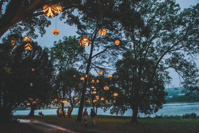 Tom Raffield wooden lights hanging up in trees.