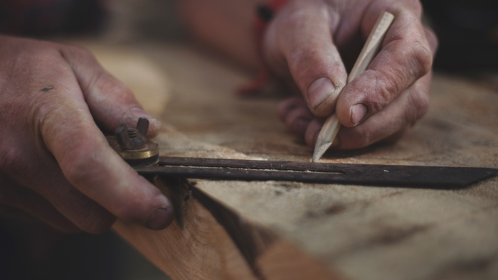 A Tom Raffield craftsman measures and marks wood with a ruler and pencil.