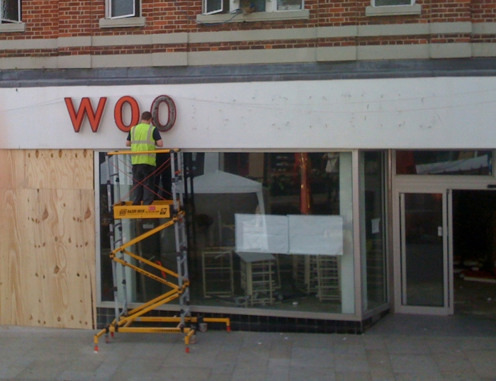 A man taking down the neon signage at a closed-down Woolworths.