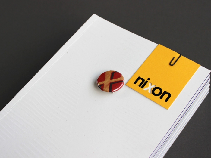 The Nixon book, with a badge and business card attached to the front.