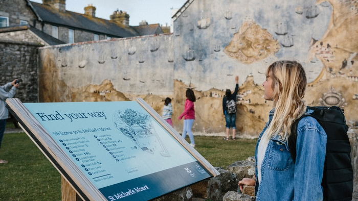 A woman looking at an information sign on St Michael's Mount.