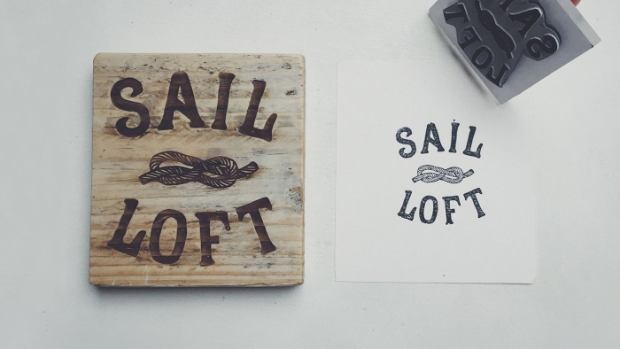 The Sail Loft word mark lasered onto wood and stamped onto a piece of paper.