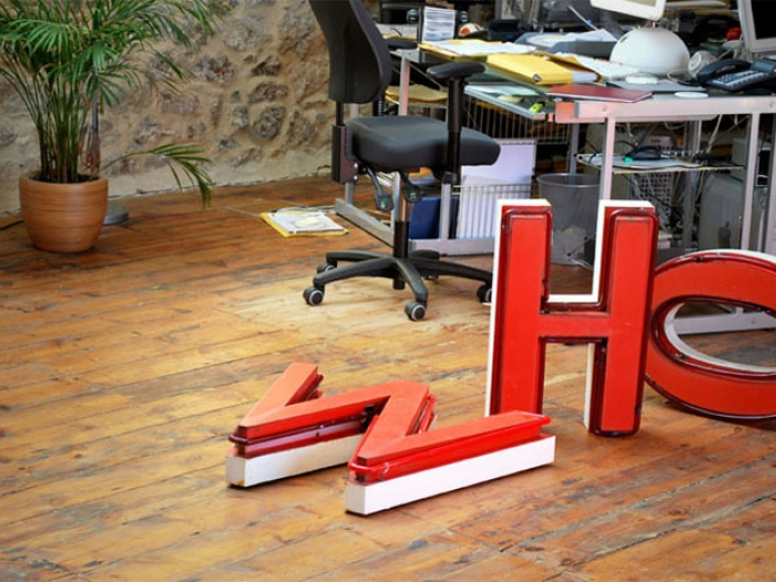 The Nixon Design studio, with wooden flooring and neon letters W, H and O, from an old Woolworth's sign.