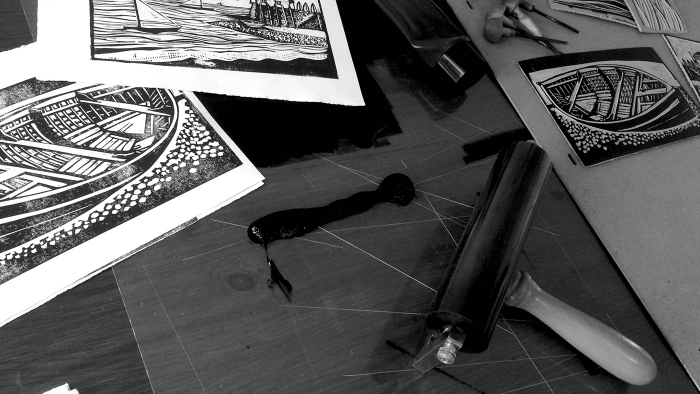 Linocut prints, a roller and other illustration tools.