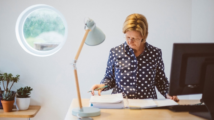 A woman looks through a folder at her desk in Latitude50's bright office space.