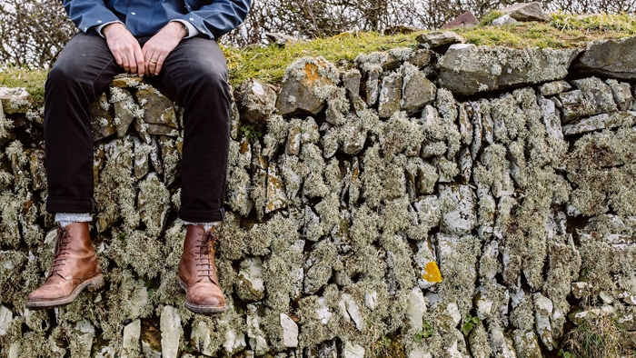 The legs of a young man who's sitting on a wall of old, lichen-covered stones.