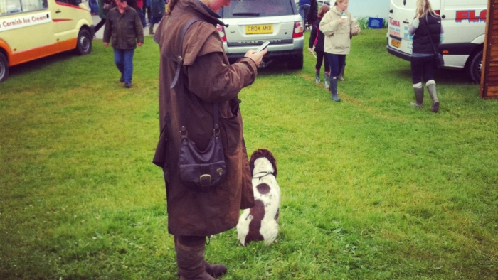 A woman looking at her phone with a dog at her feet at Royal Cornwall Show.