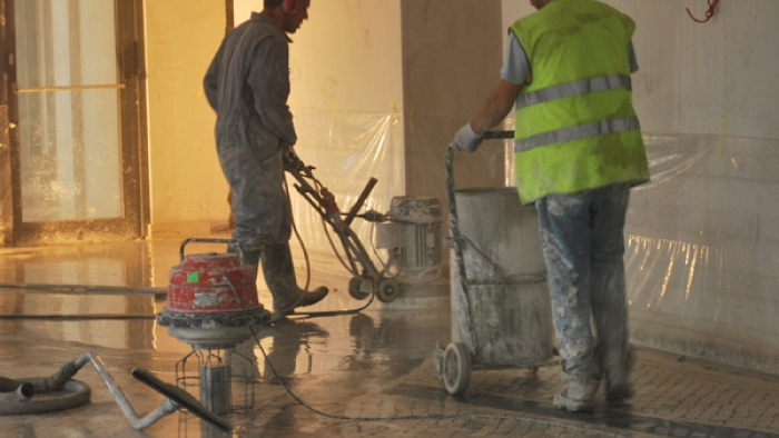 Two men working on a tiled area in a new building.