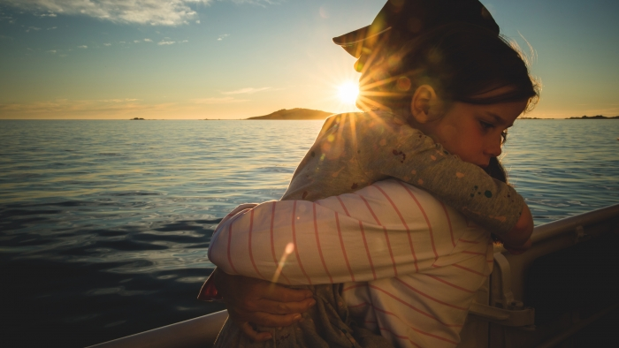 A father and daughter hug on a boat near Tresco.