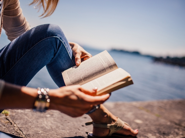 A woman reading a book, sat on a wall by the sea.
