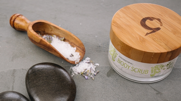 A pot of Gaia body scrub beside a wooden scoop of salt and lavender.