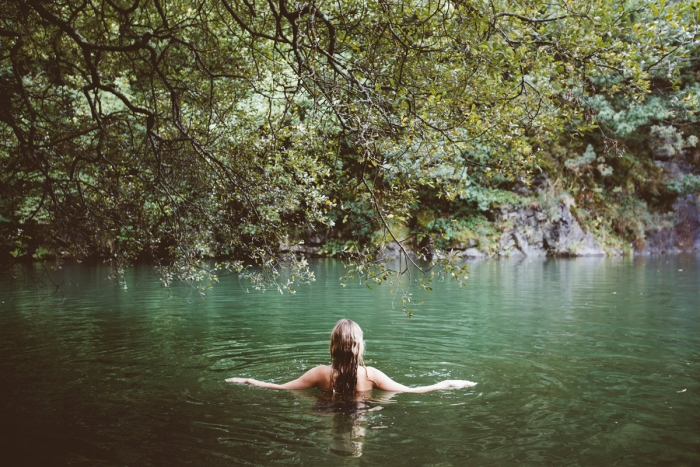 A woman swimming in a tranquil lake.