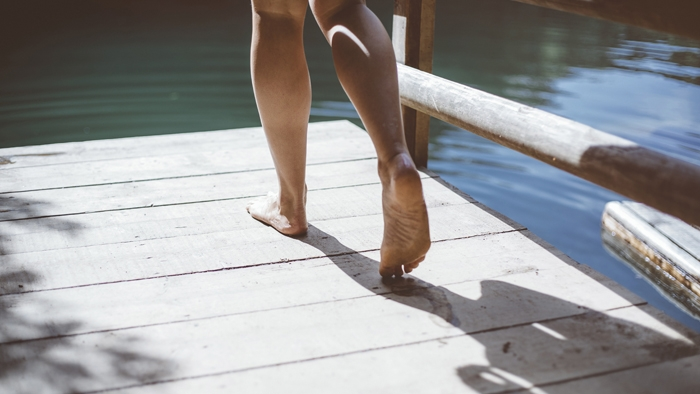 Bare feet walking on a wooden pontoon over a lake.