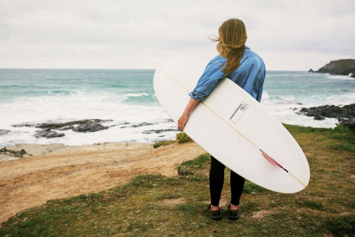 A woman holding a surfboard stands on the Cornish coast looking out to sea.