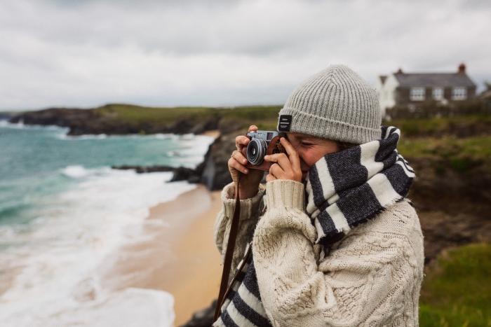 A woman stands on the Cornish coast wearing a woolly hat, scarf and jumper, taking a photo on a vintage camera.