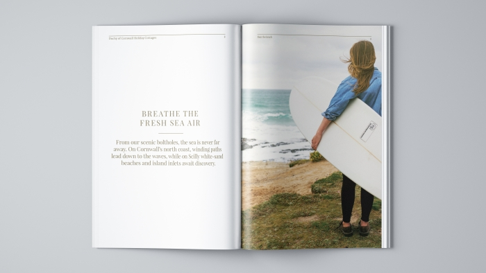 A spread in the Duchy of Cornwall Holiday Cottages brochure with text on the left an a women with a surfboard on the right.