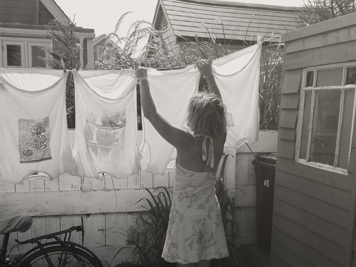 A woman hanging washing on a line.