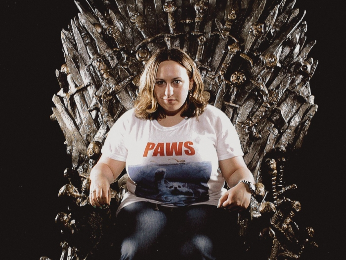 A woman sits the Iron Throne.
