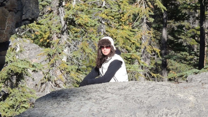 A woman in winter gear sitting on a rock beside an evergreen forest.